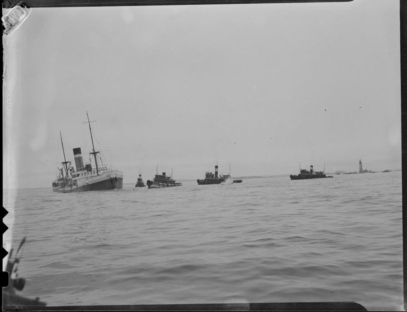 Boats help offload cargo from the City of Salisbury as it lists to starboard, prior to splitting in two atop Graves Ledge.