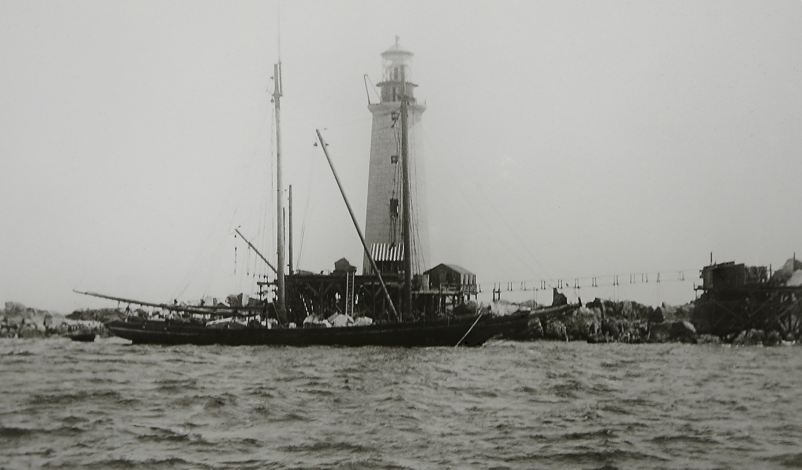 The lighthouse nears completion in mid-summer 1905. A 110-ton stone schooner delivers granite boulders to build riprap breakwaters to protect the beacon from the sea. (Photo courtesy of the Massachusetts Historical Society)