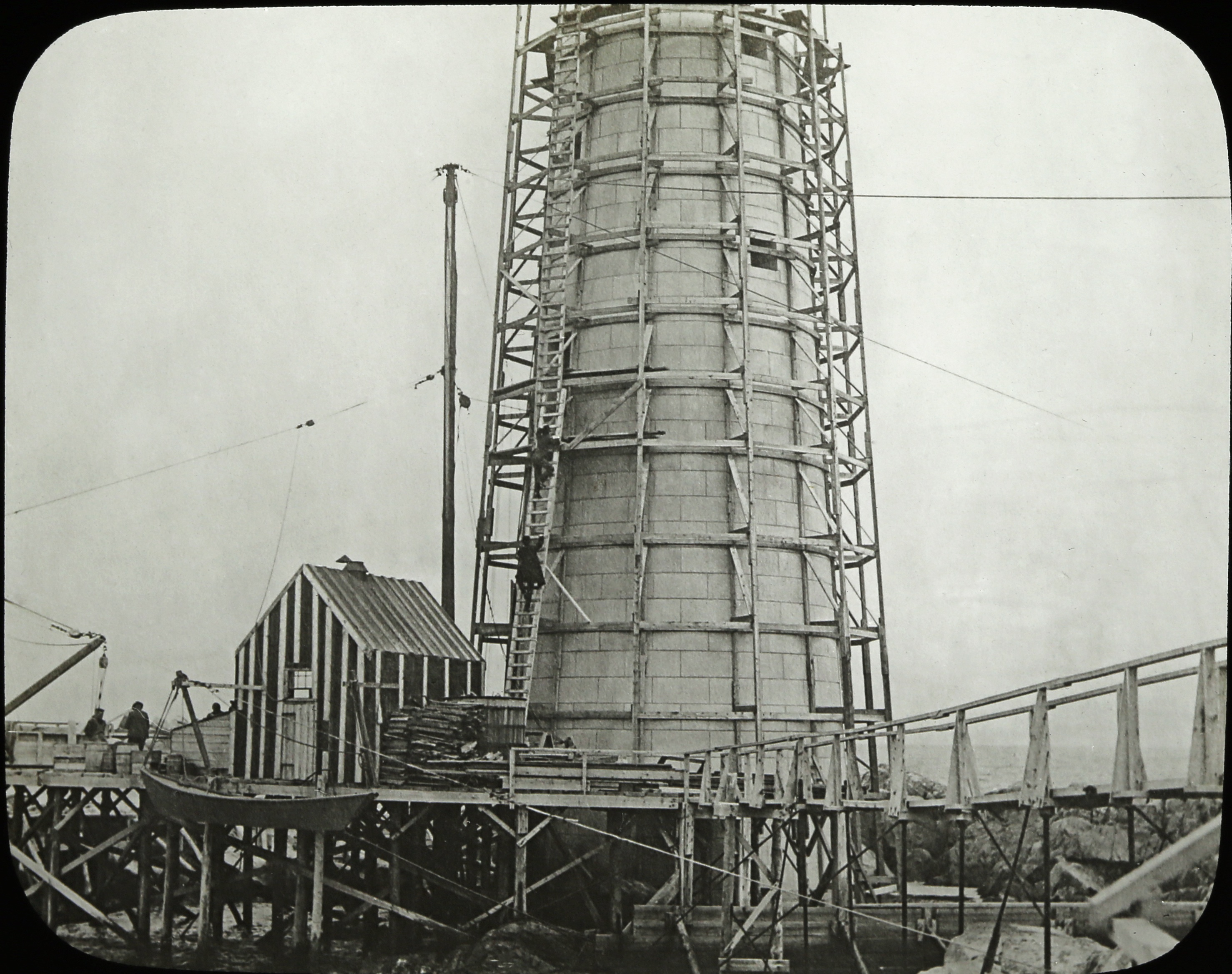 Wooden scaffolding surrounds the new tower as the builders proceed in 1904. Some of the construction shanties apparently remained for a few years after completion. (Photo courtesy of the Massachusetts Historical Society)