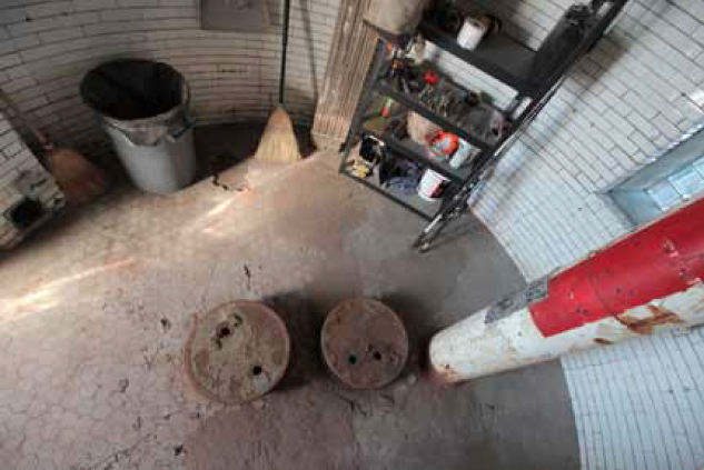 The floor of level 1. The two circular iron caps are the covers for the cisterns - one for fresh water and one that was used for compressed air to power the fog horn, and later to store fuel.