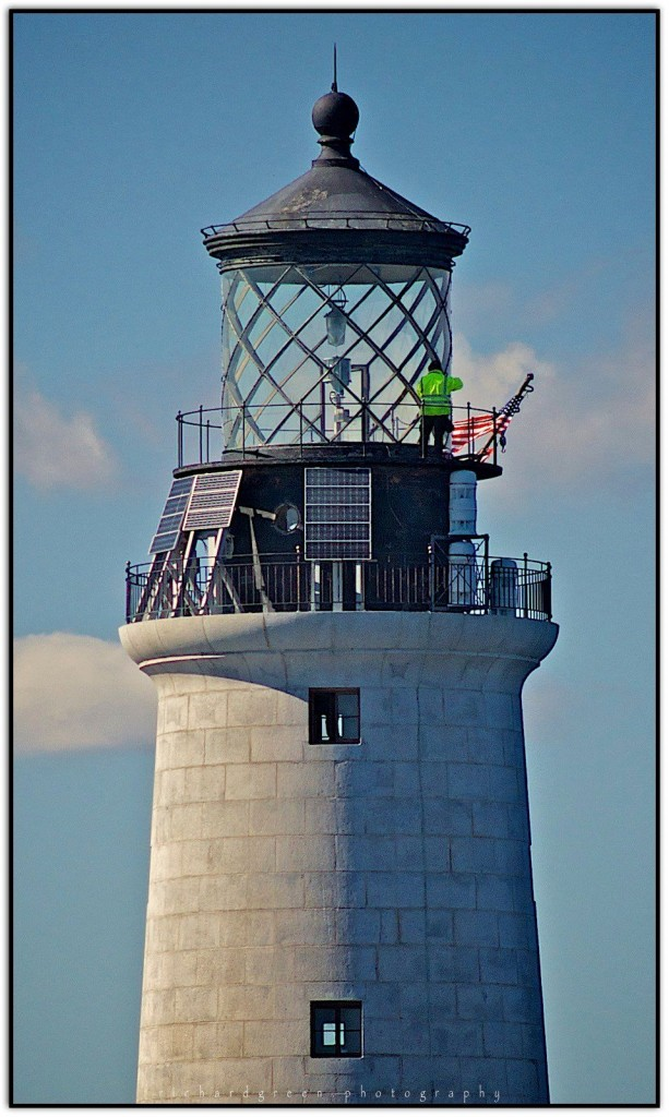 Pedro is up on the lamp deck, a hundred feet above the rocks, glazing the windows. Photo by Richard Green, who was passing by on the 'Freedom.'
