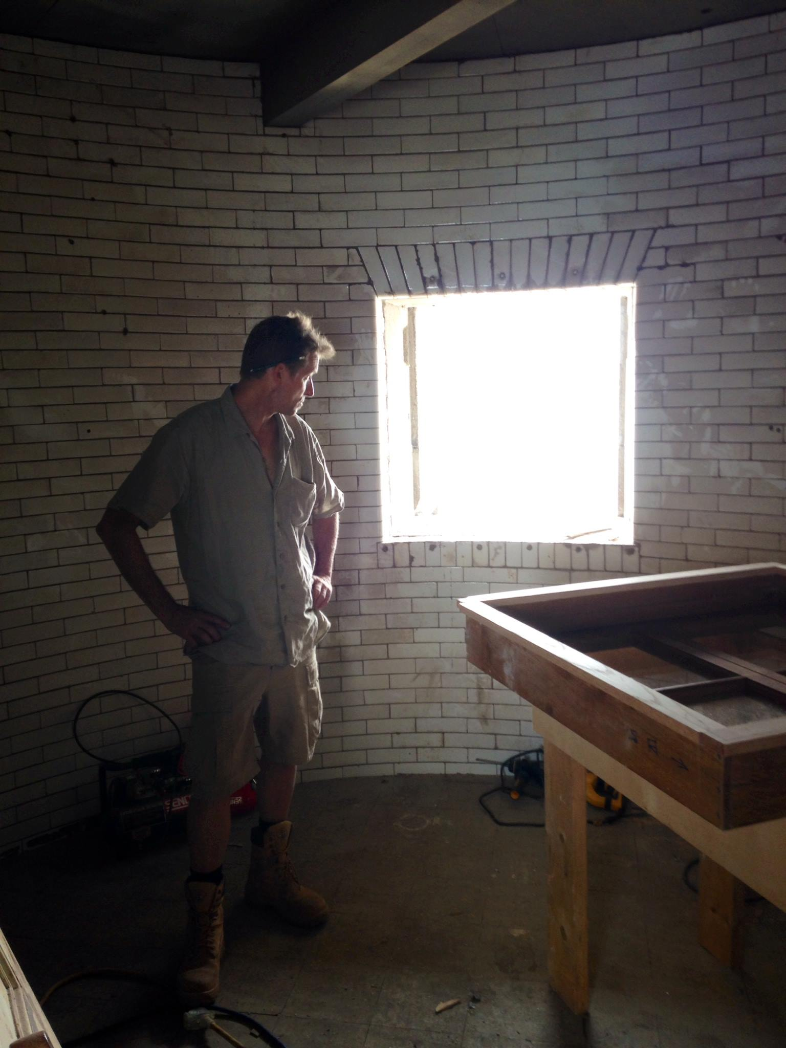 Karl Phillips of Driftwood Construction in Nantucket looks at how he's going to install the white oak casement window he built to restore the Graves Light windows to their original appearance and function.