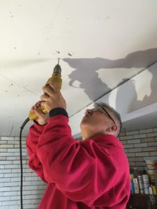 Art Graves drills into the cast iron ceiling to prepare installation of restored ship's lanterns.