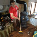 Dave sweeps up by the first fire in Graves Light's new potbelly stove.