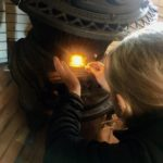 Mary lights the potbelly stove for the first time.